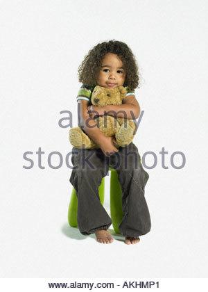 Girl hugging a teddybear - Stock Photo