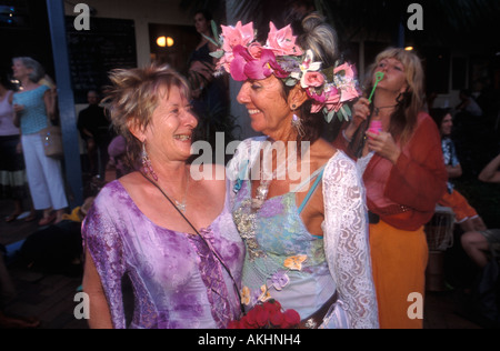 Two colourfully dressed middle-aged women celebrate Christmas eve at street party in Bangalow , N.S.W , Australia - Stock Photo