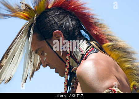 Profile of a Native American wearing a feathered headdress - Stock Photo