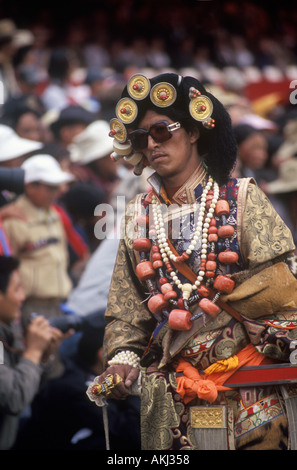 Male Khampa wears tiger skin coral zee stones gold gau boxes at the Litang Horse Festival Sichuan Province China - Stock Photo