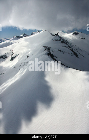Aerial of snow covered mountain with clouds in Crystal Range California USA - Stock Photo