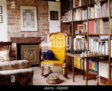 Yellow armchair and chess set on table in front of bookshelves in country living room with fireplace in exposed - Stock Photo
