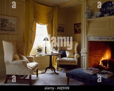 Cream wingchairs in cream panelled livingroom with yellow swagged curtains and lighted fire in fireplace - Stock Photo