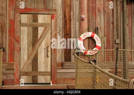 A water bouey hanging next to a door an a building with red worn wood siding along the docks - Stock Photo
