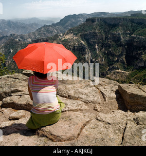 woman Looking out onto Copper Canyon mountain range holding orange red parasol umbrella shade - Stock Photo