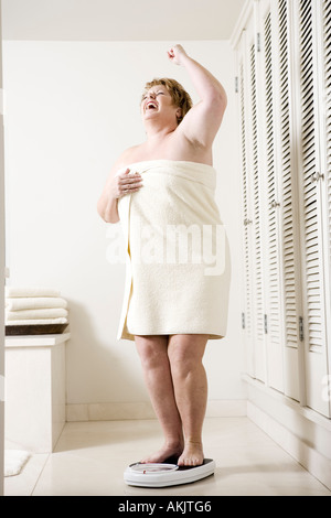 Happy overweight woman on bathroom scale - Stock Photo
