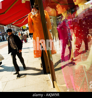 Sikh young man walking past reflections in sari shop window high street retail Southall West London - Stock Photo