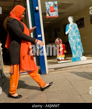 muslim or sikh woman in bright orange traditional clothing walking past indian travel agent window high street Southall - Stock Photo