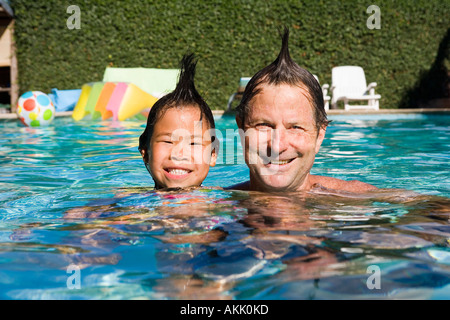 Father and daughter with mohawks in pool - Stock Photo