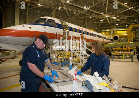 Workers do heavy maintenance on American Eagle Embraer jet airplanes at Sawyer International Airport - Stock Photo