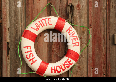A water bouey hanging an a red worn wood siding on a building along the docks - Stock Photo