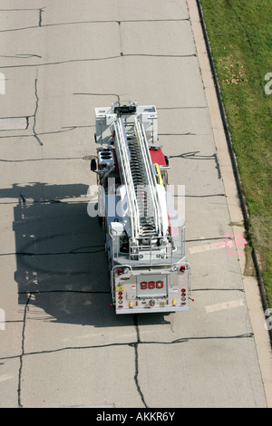 A ladder fire truck leaving an emergency scene - Stock Photo