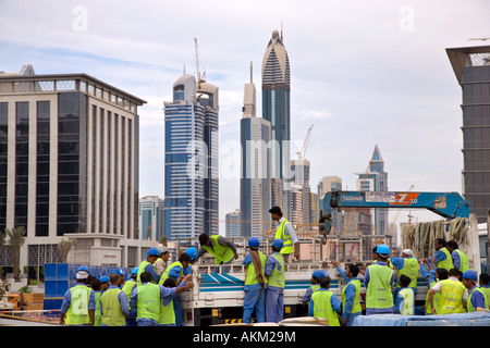 Asian workmen on site at the unfinished, incomplete skyscraper Buildings; Immigrant Foreign Construction project - Stock Photo