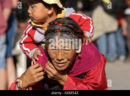 Elderly Tibetan woman carrying her grandchild on her back Lhasa Tibet - Stock Photo