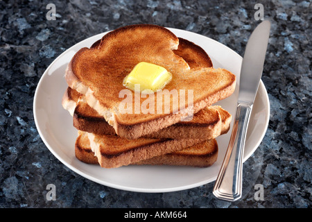 STACK OF FOUR SLICES OF TOAST WITH CHUNK OF MELTED BUTTER ON TOP WHITE PLATE KNIFE AND GRANITE TABLETOP - Stock Photo