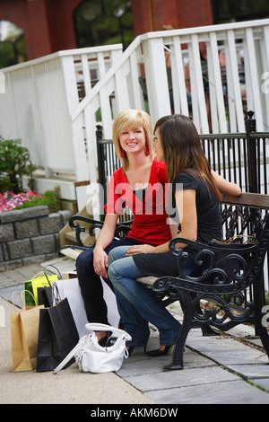 Friends sitting on a bench after shopping - Stock Photo