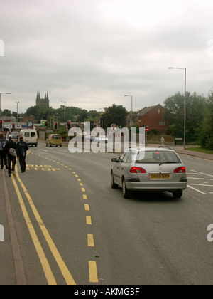 Road Junction Upper Gungate Tamworth. A car passing a Bus Stop. People are walking on double yellow lines in the - Stock Photo