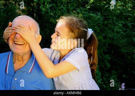 Guess Who Little girl surprises grandad who she adores - Stock Photo