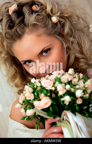 A beautiful blonde bride seen here in a wedding dress smelling her bouquet of flowers on her wedding day - Stock Photo