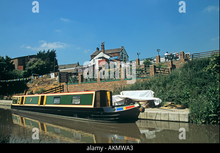ANDERTON NORTHWICH CHESHIRE England UK Narrow boat moored on the Trent and Mersey Canal with a canal side pub in - Stock Photo