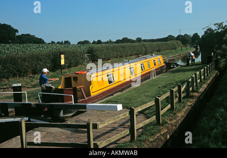 COXBANK CHESHIRE UK Yellow narrowboat waiting in lock No 13 on the Shropshire Union Canal  male friend waiting to - Stock Photo