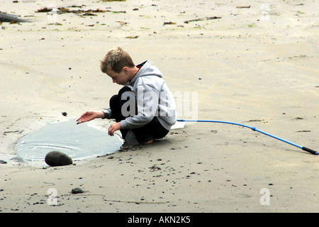 Young boy playing by himself on beach at Mullaghmore harbour, County Sligo, Ireland - Stock Photo