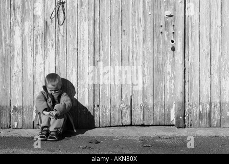 Stock Photo of a Young boy sitting with his head bowed in front of a wooden door - Stock Photo