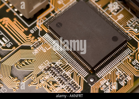 Digital close up photograph of the insides of a computer circuit board including a computer chip and circuits - Stock Photo