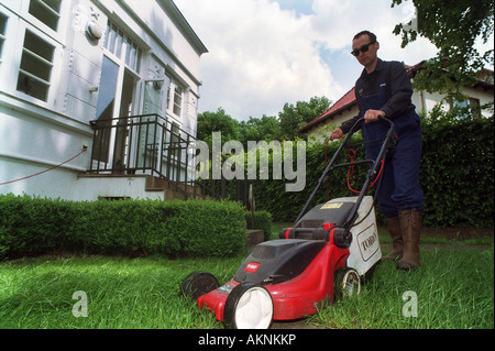 Man mowing the lawn in his garden, Verden, Germany - Stock Photo