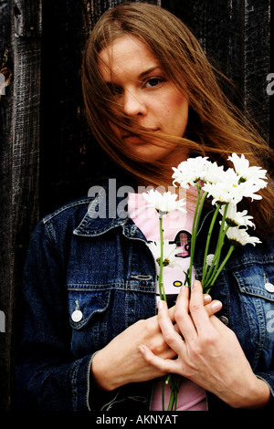 Young woman holding flowers - Stock Photo