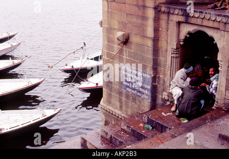 Ghat steps in Varanasi wooden ferry row boats parked neatly on the water - Stock Photo