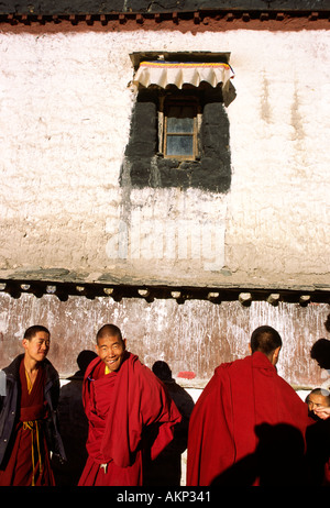 Three young male Buddhist monks in red robes in the courtyard of the Sakya Monastery Tibet China Asia - Stock Photo