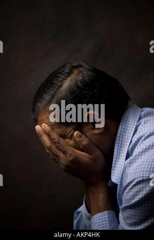 Indian man head in hands - Stock Photo