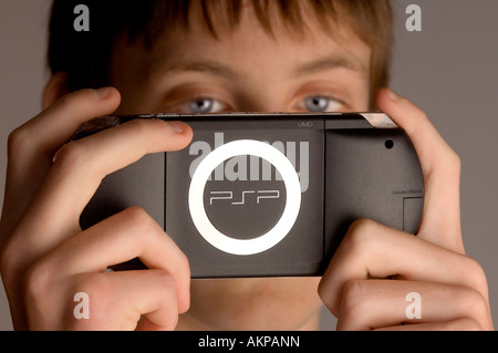 A young teenage boy playing on Sony PSP hand-held computer game console. - Stock Photo