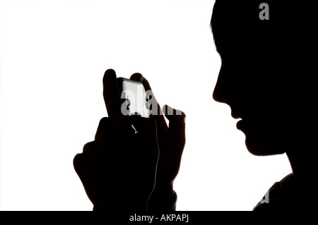 A silhouette of a young teenage boy playing on Sony PSP hand-held computer game console. Picture by Jim Holden. - Stock Photo