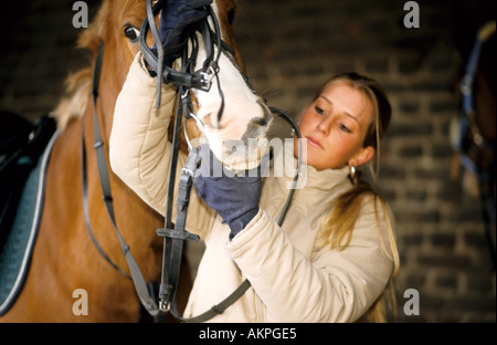 Germany Free time Two young women on a stud farm putting on the bridle  - Stock Photo