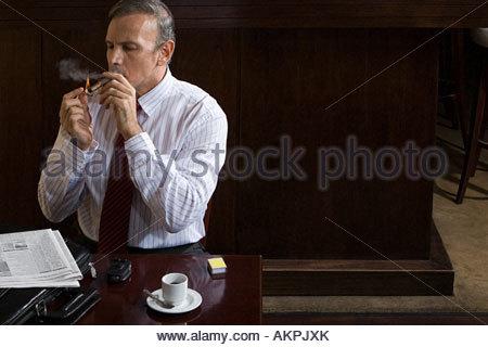 Businessman smoking cigar - Stock Photo
