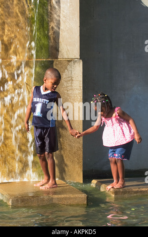 Young Boy Holding Sisters Hand and Helping Her Cross to Stepping Stone Fountain Belvedere Louisville Kentucky - Stock Photo