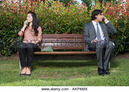 People using different phones on bench - Stock Photo