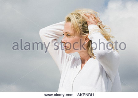 Woman with hands in hair - Stock Photo
