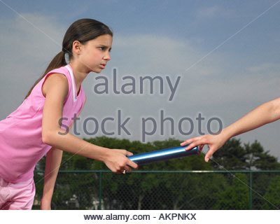 A girl passing the baton - Stock Photo