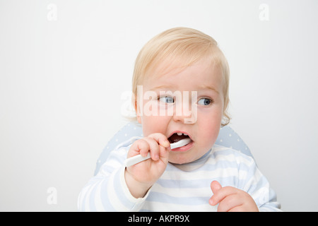 A baby boy brushing his teeth - Stock Photo