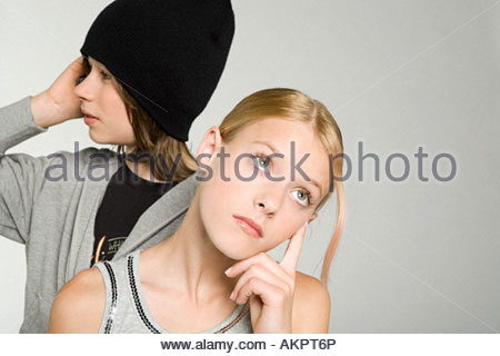 A bored teenage girl waiting for a teenage boy - Stock Photo