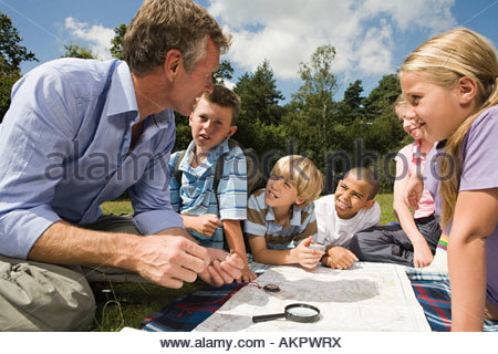 Teacher and pupils with map - Stock Photo