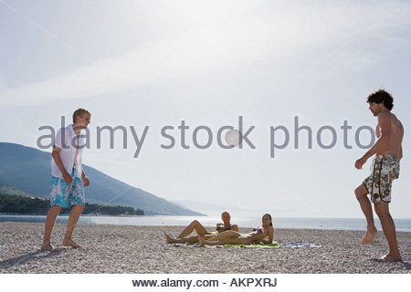 Young men playing football on the beach - Stock Photo