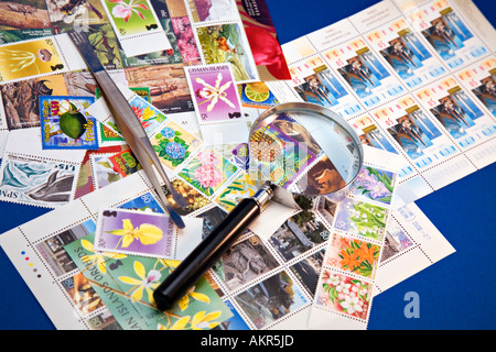 Stamp collection with magnifying glass and tongs - Stock Photo