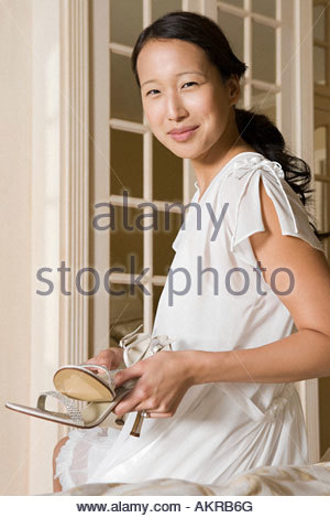 Bride holding shoes - Stock Photo