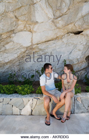Couple sitting on wall - Stock Photo