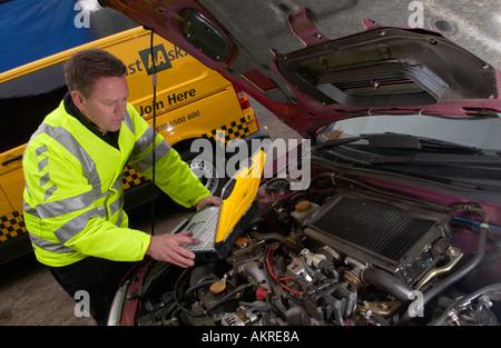 AA patrolman using his laptop diagnostic toolkit at a roadside breakdown UK GB - Stock Photo