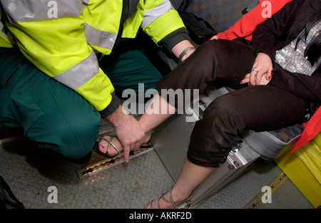 Paramedic checking the mobility of a young womans knee after she fell on St Marys Street Cardiff she had to much - Stock Photo
